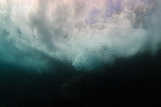 Underwater view of waves crashing against rocks producing bubbles, foam and spray