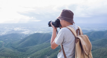 Photographer using Camera DSLR, Digital Single Lens Reflex take a photo Mountain and blue sky. Traveling Concept. Hiker concept.
