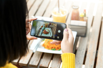 Young hipster asian blogger take photo of food, plate, healthy recipe, lunch meal, breakfast share to story content in social media at restaurant or home. Screen on moblie phone with blogger concept.