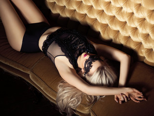 Beautiful and young woman posing in lingerie and Venetian mask on sofa. Vintage interior and retro background.