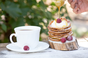 A stack of delicious pancakes with honey and blueberries on a wood background. with copy space