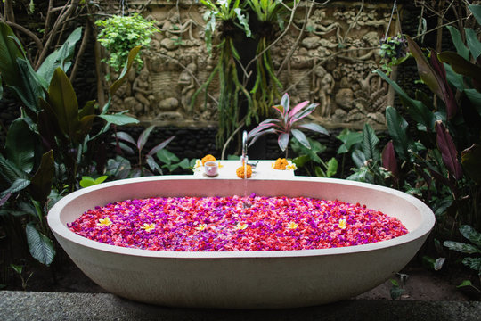 Luxury hotel bathroom with red and pink tropical flowers, spa concept  Bathtube with petals in tropics. Time for yourself.