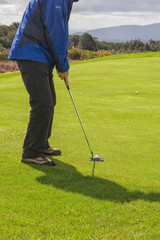 Golfer putting on green