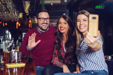 Three friends taking selfie in a bar. - Image