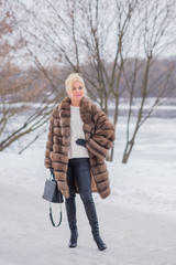 Nice elegant lady in fur coat at nature, autumn - winter season time, woman with attractive appearance