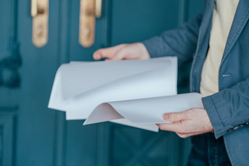 The man in blue jacket suit holding sheets of paper in his hands, close up