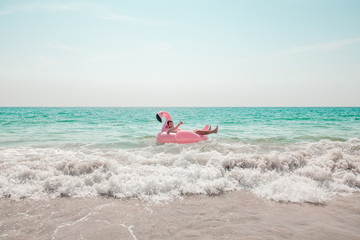 A man is having fun on pink flamingo inflatable pool float in the turquoise sea with white waves