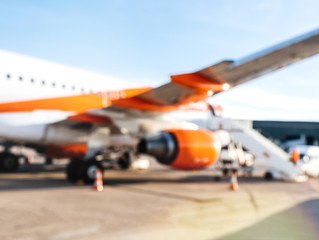 Defocused view of modern aircraft at the international airport tarmac waiting for passengers on a bright sunny day