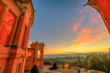 Landscape of hills above Bologna from a window on the portico of San Luca Sanctuary with a scenic sunset light. Side view of arcades of the portico. Aerial view on the church courtyard.
