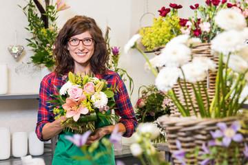 Freudig lächelnde Floristin mit frisch gebundenem Valentinsstrauß
