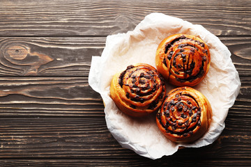 Buns with cinnamon and chocolate on a brown wooden background. Cinnamon stick and black espresso coffee. Place for text. Top view.