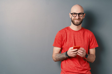 Handsome hairless Caucasian man with beard, glasses, red T-shirt holding smartphone in his tattooed arms on gray studio background