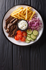 Freshly cooked shawarma plate with beef, french fries, vegetables and sauce close-up. Vertical top view