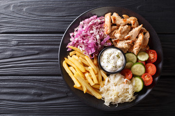 Doner kebab on a plate with french fries, salad and sauce close-up on a table. Horizontal top view