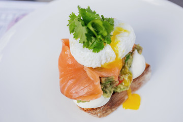 Toast with guacamole, salmon and poached egg.