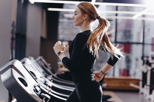 The athletic girl dressed in a black sportswear running on the treadmill in the modern gym