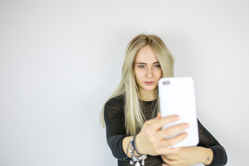 Modern blonde takes a selfie on the phone