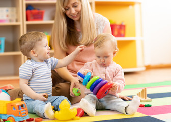 cute babies play with carer in nursery or kindergarten
