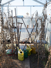 watering cans and garden tools wait in greenhouse during winter