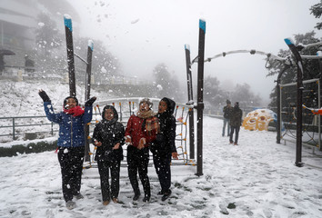 People pose for a picture as they play with snow during a snowfall on Chandragiri Hills in Kathmandu