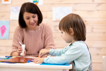 Child girl with kindergarten teacher working with color paper