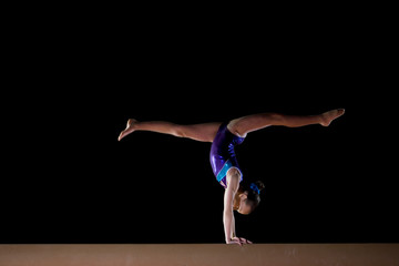 Female gymnast performing handstand on gymnastic balance beam
