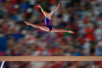 Young female gymnast performing splits in air above balance beam
