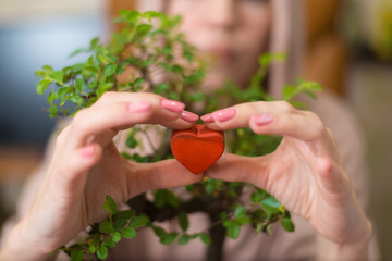 Woman holding a wooden red heart in the background of a bonsai tree.