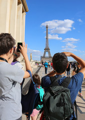 young tourists photograph the Eiffel Tower