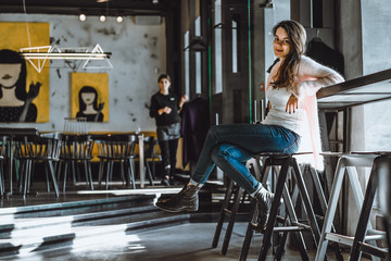 beautiful brunette girl in cafe with interior in loft style
