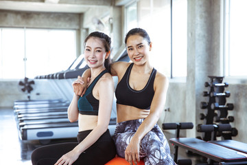 Two young beautiful woman relax in gym