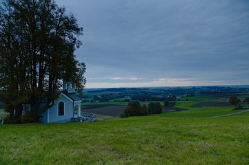 View over the Isental in Bavaria in the morning with a small chapell in the foreground