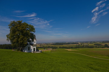 Scenic view over the Isental in Bavaria with a small chapell in the foreground