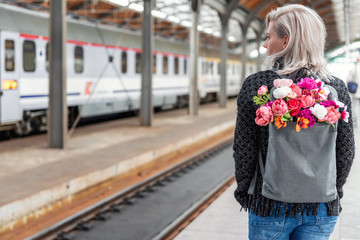 Blonde attractive woman with bouquet of flowers in grey backpack is waiting for train. Photo from the back. Tryst concept