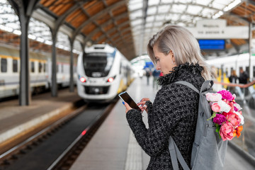 Blonde attractive woman with bouquet of flowers in grey backpack is holding smartphone and waiting train, side view.