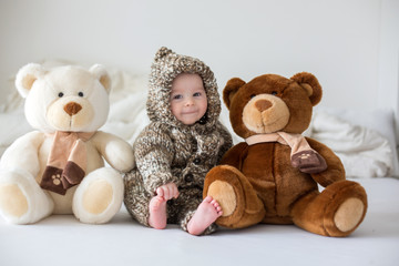 Little baby boy playing at home with soft teddy bear toys, lying down