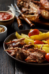 Roasted turkey legs with potatoes and tomatoes, on dark wooden background.