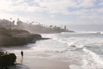 Man standing on the beach at the coast of the Pacific Ocean in San Diego. The waves cause a mist of sea water.