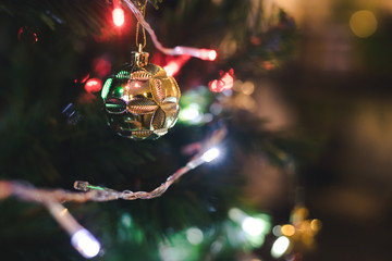 close up of golden ball hanging on Christmas tree as a prop over LED light line