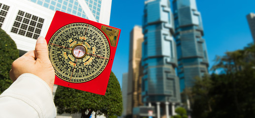 Feng Shui Master show FengShui Compass and turn direction to Force Energy, He wear black shirt to check North South West East for Luck and Prosperity to Design Building on Wind Water elements Signs Wall mural