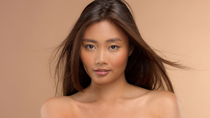 beauty asian thai japanese model with blowing straight hair watching to the camera
