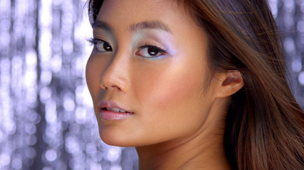 thai asian model in studio with silver rain disco background and party makeup Closeup portrait