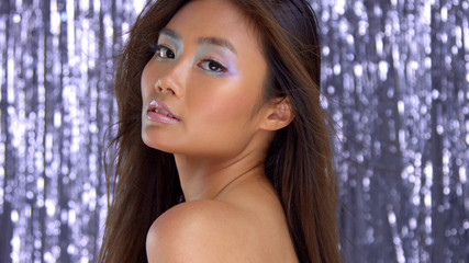thai asian model in studio with silver rain disco background and party makeup Ideal skin, highlight makeup