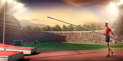 Young male pole vault athlete with pole bar. Men in sport clothes at athletic sport track in professional stadium