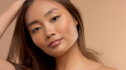 closeup portrait of asian model touching her straight hair