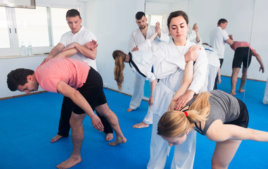 trainees sparring in pairs to practice new holds in taekwondo class