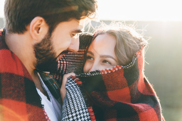 Young beautiful couple walking outside on beautiful sunset. Perfect romantic landscape for lovestory. Two hipsters-lovers hugging and kissing. Valentine's day concept.