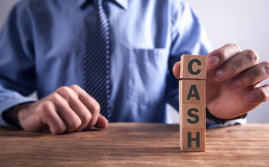 Man showing word Cash with wooden blocks.