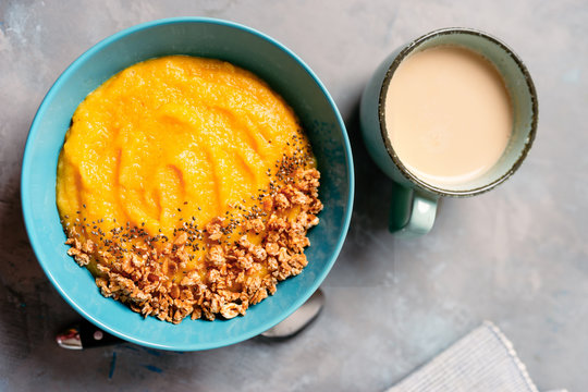 Top view of yellow smoothie bowl with granola