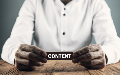 Man holding Content word on wooden block.